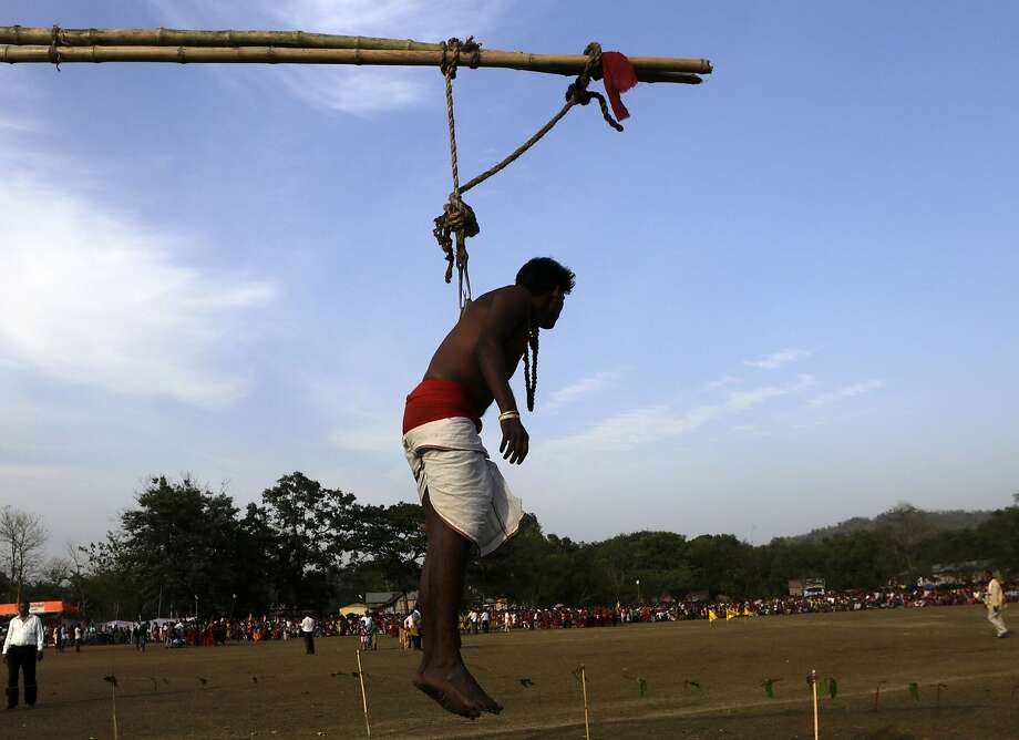 An Indian Hindu devotee is hung on a rope with metal hooks pierced into his back as he performs a ritual during the Suwori festival in Boko, Assam state, India, Sunday, April 20, 2014. The festival coincides with Rongali Bihu, the harvest festival of this northeastern state. (AP Photo/Anupam Nath) Photo: Anupam Nath, Associated Press