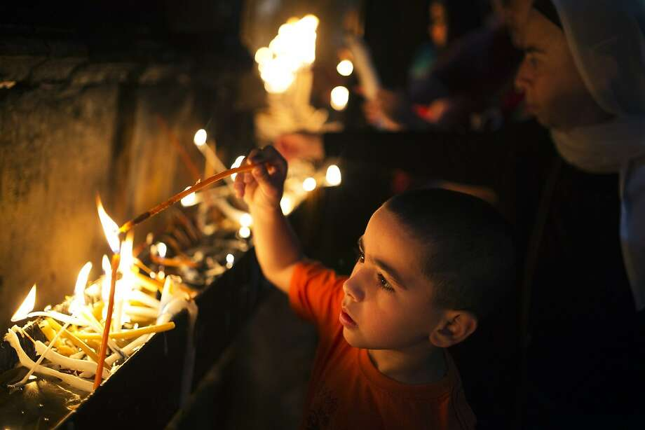 A Christian boy lights a candle inside the Church of the Holy Sepulchre before the Easter Sunday mass procession in Jerusalem's old city April 20, 2014. REUTERS/Amir Cohen (JERUSALEM - Tags: RELIGION) Photo: Amir Cohen, Reuters