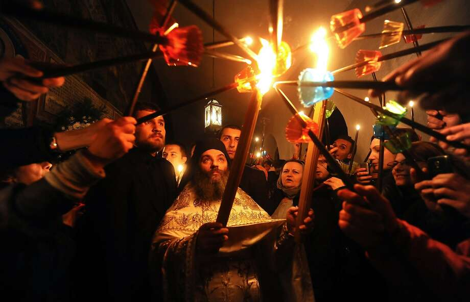 Macedonian Orthodox Christians light candles from the holy fire that arrived from Jerusalem during an Easter service at the Saint Jovan Bigorski monastery, some 145 km west from the capital Skopje, in Macedonia, on April 20, 2014.The Macedonian Orthodox Church celebrated Easter, according to the Julian calendar. AFP PHOTO / ROBERT ATANASOVSKIROBERT ATANASOVSKI/AFP/Getty Images Photo: Robert Atanasovski, AFP/Getty Images