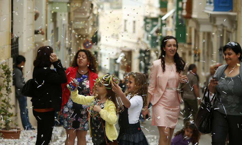 Children play with confetti before a statue of the Risen Christ is carried during an Easter Sunday procession in Cospicua, outside Valletta April 20, 2014.  REUTERS/Darrin Zammit Lupi (MALTA - Tags: RELIGION SOCIETY) MALTA OUT. NO COMMERCIAL OR EDITORIAL SALES IN MALTA Photo: Darrin Zammit Lupi, Reuters