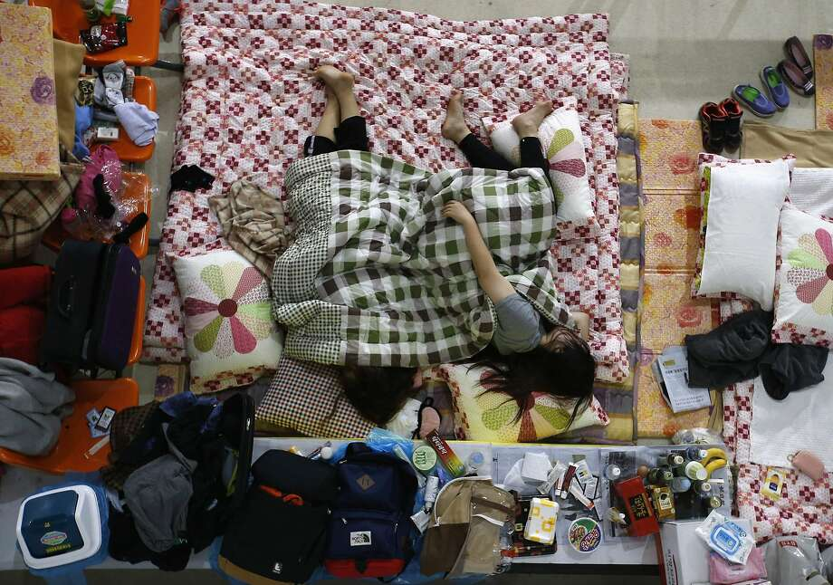 Family members of missing passengers onboard the South Korean ferry Sewol which capsized on Wednesday, rest in makeshift accommodations at a gymnasium in the port city of Jindo, April 21, 2014. The captain of a ferry that sank off South Korea's southwestern tip with hundreds feared dead said in a promotional video four years ago that the journey was safe - as long as passengers followed the instructions of the crew.  REUTERS/Kim Kyung-Hoon (SOUTH KOREA - Tags: DISASTER MARITIME) Photo: Kim Kyung-hoon, Reuters