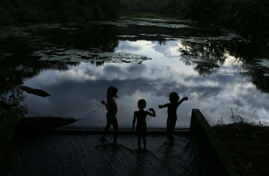 Children play at the edge of a lagoon at the Ecological Reserve of Guapiacu (REGUA) in Rio de Janeiro April 19, 2014. Picture taken April 19, 2014. REUTERS/Pilar Olivares (BRAZIL - Tags: ENVIRONMENT) Photo: Pilar Olivares, Reuters