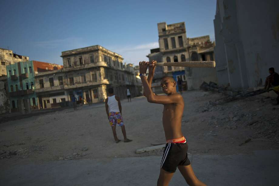In this April 12, 2014 photo, youngsters play baseball next to rundown buildings in Havana, Cuba. The country lacks around 500,000 units of housing according to the most recent government numbers from 2010. The problem grows each year as more buildings fall further into disrepair, punished year-round by the tropical sun, sea and wind.(AP Photo/Ramon Espinosa) Photo: Ramon Espinosa, Associated Press