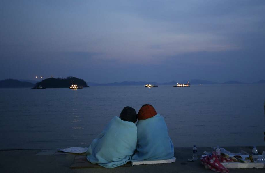 Relatives of passengers aboard the sunken ferry Sewol sit near the sea at a port in Jindo, south of Seoul, South Korea, Sunday, April 20, 2014. After more than three days of frustration and failure, divers on Sunday finally found a way into the submerged ferry off South Korea's southern shore, discovering more than a dozen bodies inside the ship and pushing the confirmed death toll to over four dozens, officials said. (AP Photo/Lee Jin-man) Photo: Lee Jin-man, Associated Press
