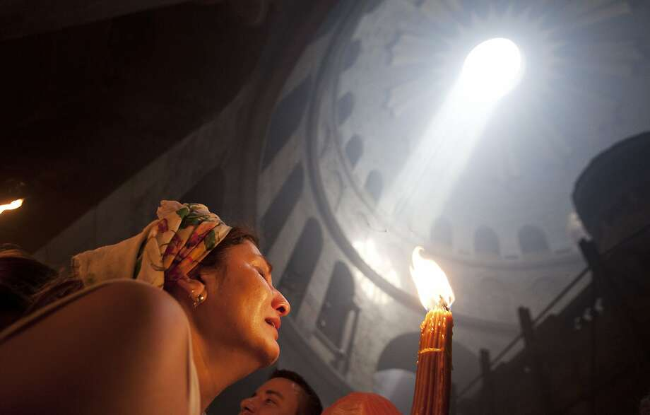 "A Christian pilgrim holds candles at the church of the Holy Sepulcher, traditionally believed to be the burial site of Jesus Christ, during the ceremony of the Holy Fire in Jerusalem's Old City, Saturday, April 19, 2014. The ""holy fire"" was passed among worshippers outside the Church and then taken to the Church of the Nativity in the West Bank town of Bethlehem, where tradition holds Jesus was born, and from there to other Christian communities in Israel and the West Bank. (AP Photo/Dan Balilty) Photo: Dan Balilty, Associated Press"