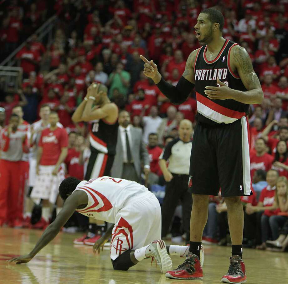 Rockets guard Pat Beverley, left, tries to get up after taking a charge from Trail Blazers forward LaMarcus Aldridge on Sunday night at Toyota Center. The charge fouled out Aldridge, who had torched the Rockets for 46 points and 18 rebounds in Portland's 122-120 overtime victory in Game 1 of the best-of-seven opening series. Photo: James Nielsen, Staff / © 2014  Houston Chronicle