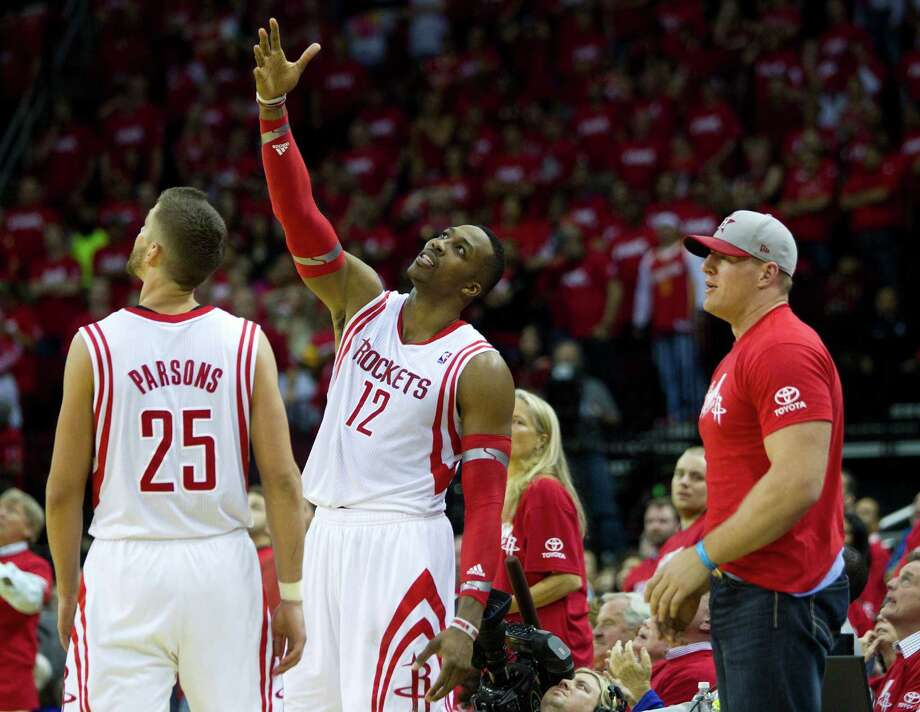 An incredulous Dwight Howard, center, can't believe he fouled out late in the Rockets' playoff-opening loss to the Trail Blazers on Sunday, while Chandler Parsons, left, and J.J. Watt can do little to console him. Photo: Brett Coomer, Staff / © 2014 Houston Chronicle