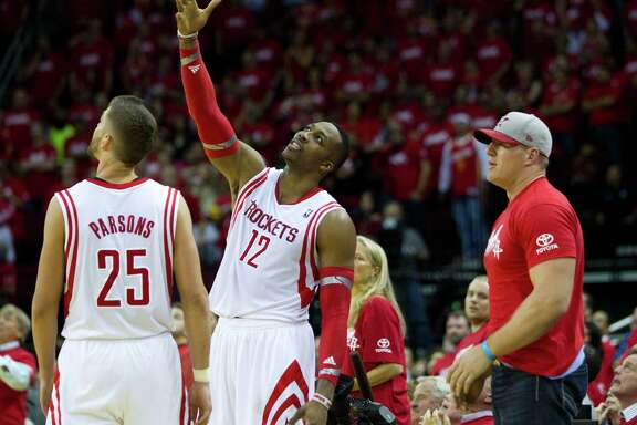 An incredulous Dwight Howard, center, can't believe he fouled out late in the Rockets' playoff-opening loss to the Trail Blazers on Sunday, while Chandler Parsons, left, and J.J. Watt can do little to console him.
