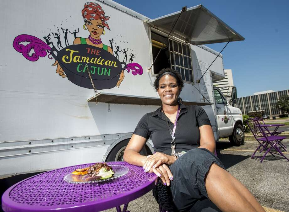 Nyjuma Howard poses for a picture next to a plate of JaCajun wings and plantains Wednesday afternoon. Howard owns and operates the Jamaican Cajun food truck, which can be found at various locations throughout the week. Photo taken Wednesday, 4/9/14 Jake Daniels/@JakeD_in_SETX