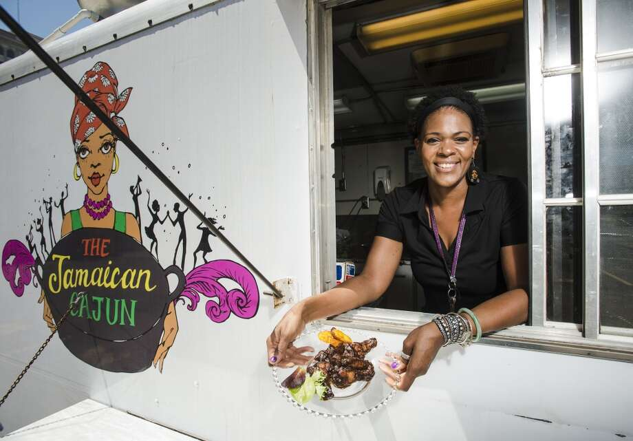 Nyjuma Howard poses for a picture with a plate of JaCajun wings and plantains Wednesday afternoon. Howard owns and operates the Jamaican Cajun food truck, which can be found at various locations throughout the week. Photo taken Wednesday, 4/9/14 Jake Daniels/@JakeD_in_SETX