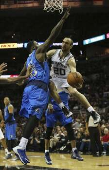San Antonio Spurs' Manu Ginobili passes around Dallas Mavericks' DeJuan Blair during the first half of game one in the first round of the Western Conference Playoffs at the AT&T Center, Sunday, April 20, 2014. Photo: Jerry Lara, San Antonio Express-News