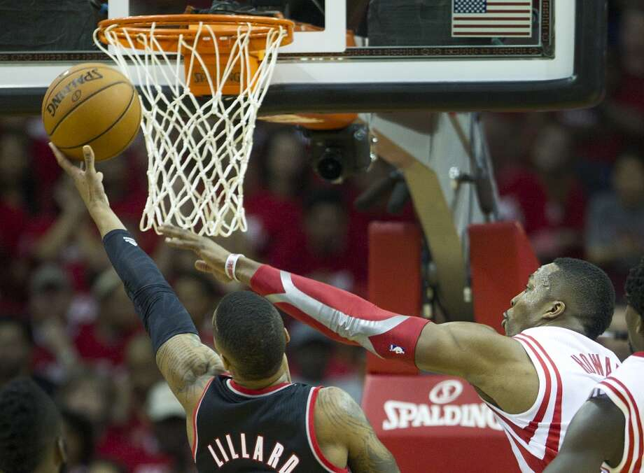 Houston Rockets center Dwight Howard, right, reaches out to defend a shot by Portland Trail Blazers guard Damian Lillard during the second quarter of an NBA playoff basketball game at Toyota Center Sunday, April 20, 2014, in Houston. ( Brett Coomer / Houston Chronicle ) Photo: Brett Coomer, Houston Chronicle