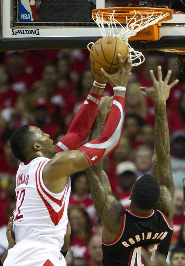 Houston Rockets center Dwight Howard (12) pulls a rebound away from Portland Trail Blazers forward Thomas Robinson (41) during the first quarter of an NBA playoff basketball game at Toyota Center Sunday, April 20, 2014, in Houston. ( Brett Coomer / Houston Chronicle ) Photo: Brett Coomer, Houston Chronicle
