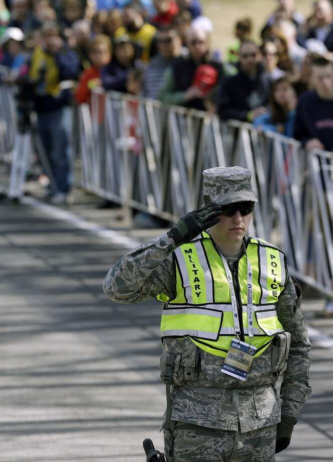 A military police officer salutes during opening ceremonies of the 118th Boston Marathon Monday, April 21, 2014 in Hopkinton, Mass.  Photo: Steven Senne, Associated Press