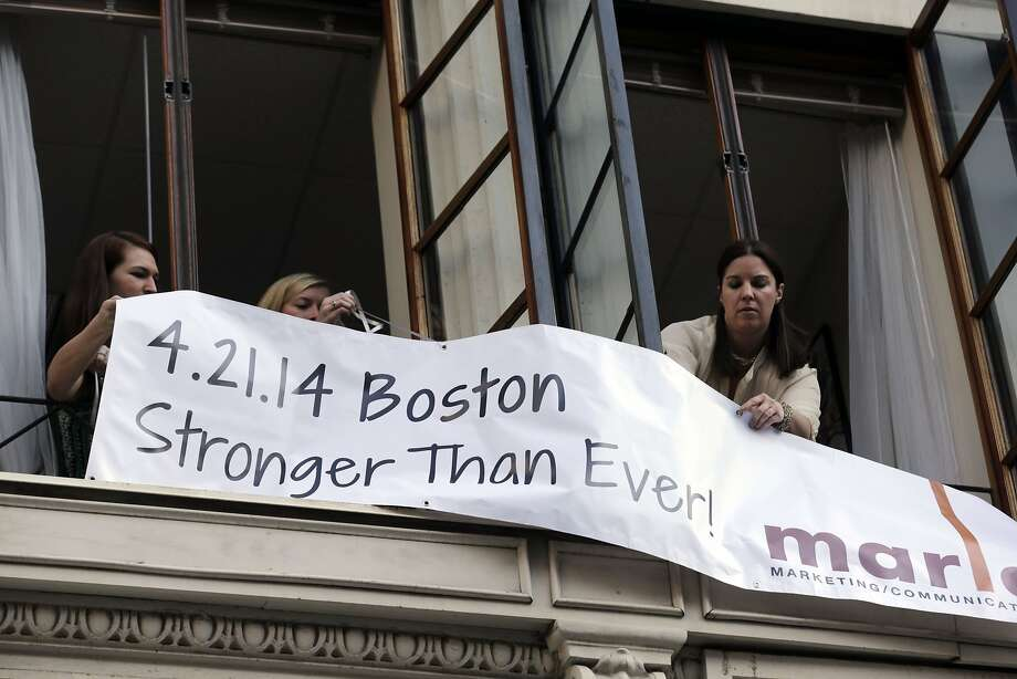 Marla Fogelman, right,  hangs a banner on the second floor over Marathon Sports store, the site of the first bomb blast in 2013, before the start of the 118th Boston Marathon Monday, April 21, 2014 in Boston.  Photo: Charles Krupa, Associated Press
