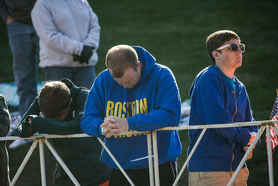 People bow their heads during a moment of silence prior to the start of the Boston Marathon  on April 21, 2014 in Hopkington, Massachusetts. Today marks the 118th Boston Marathon; security presence has been increased this year, due to two bombs that were detonated at the finish line last year, killing three people and injuring more than 260 others. Photo: Andrew Burton, Getty Images