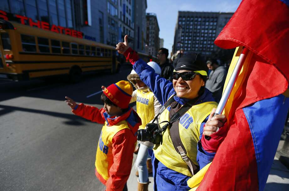 Susana Coro, of Equador, cheers with her family as buses leave Boston for the starting line in Hopkinton, Mass., for the 118th Boston Marathon Monday, April 21, 2014. The Coro family is at the race to support Susana's sister Miryam Coro, who is running.  Photo: Matt Rourke, Associated Press