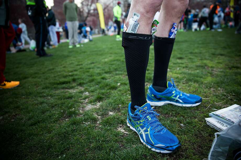 A runner tucks gel packets into his socks while getting ready to run the Boston Marathon in the Boston Commons on April 21, 2014 in Boston, Massachusetts. Today marks the 118th Boston Marathon; security presence has been increased this year, due to two bombs that were detonated at the finish line last year, killing three people and injuring more than 260 others. Photo: Andrew Burton, Getty Images