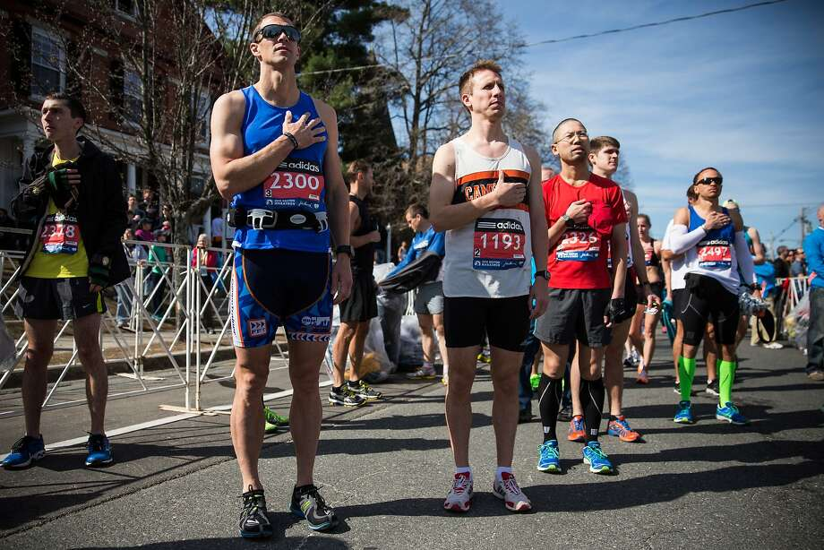 Runners place their hands over their hearts during a singing of the National Anthem at the beginning of the Boston Marathon on April 21, 2014 in Hopkington, Massachusetts. Today marks the 118th Boston Marathon; security presence has been increased this year, due to two bombs that were detonated at the finish line last year, killing three people and injuring more than 260 others.  Photo: Andrew Burton, Getty Images