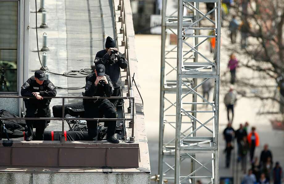 Boston Police officers patrol a rooftop along Boylston Street near the finish line during the 2014 B.A.A. Boston Marathon on April 21, 2014 in Boston, Massachusetts. Today marks the 118th Boston Marathon; security presence has been increased this year, due to two bombs that were detonated at the finish line last year, killing three people and injuring more than 260 others. Photo: Jared Wickerham, Getty Images