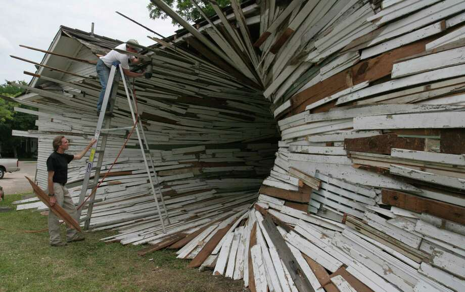 "Dan Havel, left, hands a piece of wood to Dean Ruck as they work on ""Inversion"" in Montrose in 2005. Photo: Gary Fountain, For The Chronicle / Freelance"
