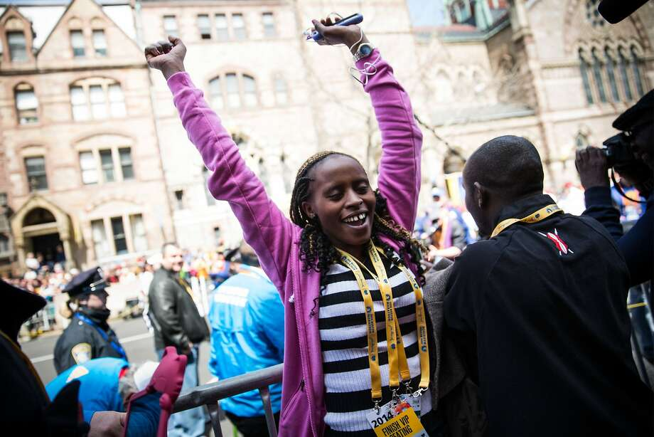 A woman dances after hugging Rita Jeptoo, of Kenya, who won in the women's division of the Boston Marathon on April 21, 2014 in Boston, Massachusetts. Today marks the 118th Boston Marathon; security presence has been increased this year, due to two bombs that were detonated at the finish line last year, killing three people and injuring more than 260 others. Photo: Andrew Burton, Getty Images