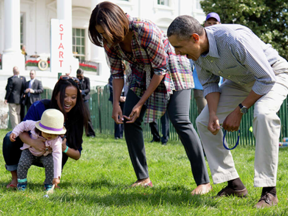 President Barack Obama and first lady Michelle Obama cheer a little egg roller as they host the White House Easter Egg Roll on the South Lawn of the White House is Washington, Monday, April 21, 2014. Thousands of children gathered at the White House for the annual Easter Egg Roll. President Barack Obama and first lady Michelle Obama kicked off the festivities on the White House South Lawn. This year's event features live music, cooking stations, storytelling, and of course, some Easter egg rolling. Photo: Carolyn Kaster, AP / AP