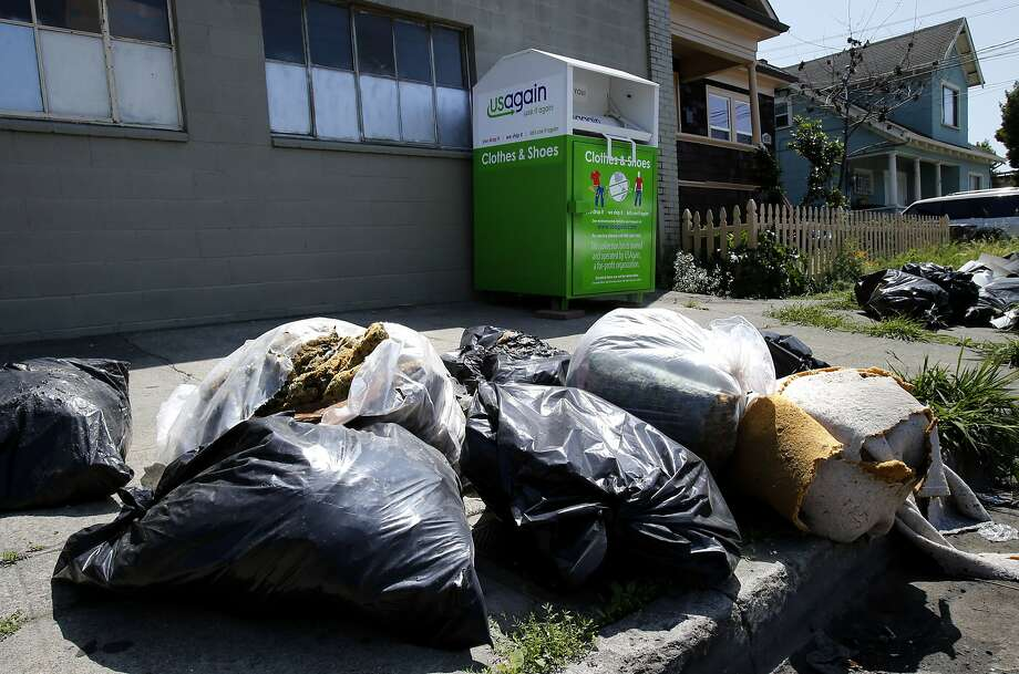 A donation box at 1212 41st Ave. is surrounded by bags of garbage and carpet debris. The Oakland City Council will consider a moratorium on donation boxes while rules are determined for them. Photo: Brant Ward, The Chronicle