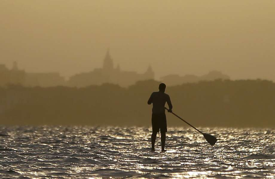 Walking on water:A paddle boarder paddles off into the sunset in Florida's Biscayne Bay off   Virginia Key. Photo: Wilfredo Lee, Associated Press