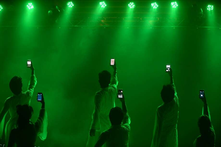 Dancing with my cellphone:HTC makes a big deal about its new line of smartphones with a lightshow and handset-wielding performers in New Delhi. Photo: Sajjad Hussain, AFP/Getty Images