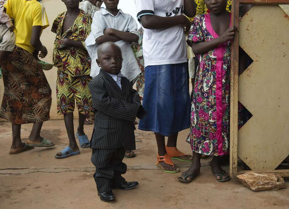 He'll grow into it: A little man in a big suit arrives for Easter celebrations at St. 