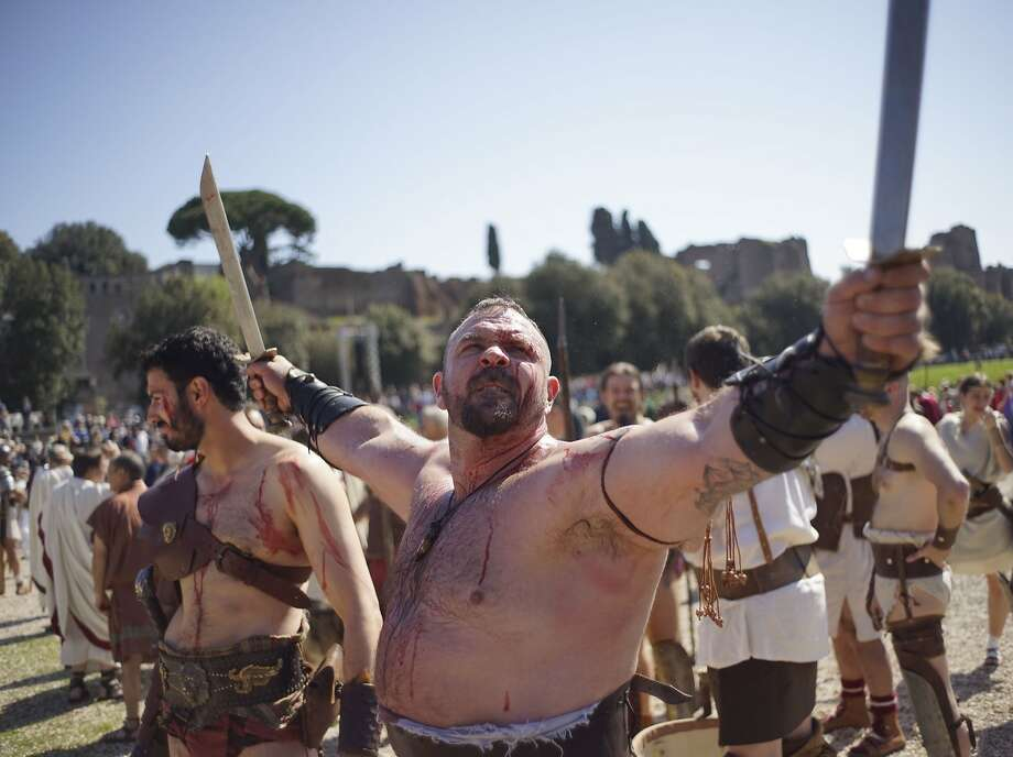 "We who are about to parade salute you: Roman ""gladiators"" prepare to march along the  ancient ruins of the Colosseum, Circus Maximus 