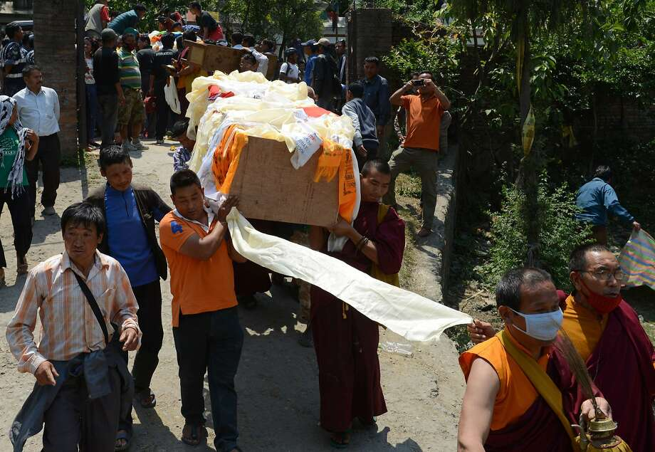 Buddhist monks lead relatives carrying a casket with the body of an Everest avalanche victim. Photo: Prakash Mathema, AFP/Getty Images