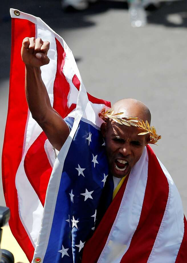 Apr 21, 2014; Boston, MA, USA; Meb Keflezighi (USA) pumps his fist while wearing an American flag at the finish line after winning the men's division of the 2014 Boston Marathon. Mandatory Credit: Greg M. Cooper-USA TODAY Sports Photo: Greg M. Cooper, Reuters