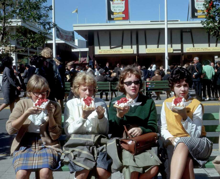 In this October 1964 photo provided by worldsfairphotos.com, four girls eat Belgian Waffles on the Grounds of the World's Fair in the Queens Borough of New York. Belgian Waffles were introduced to the American public at the fair by Belgian Maurice and Rose Vermersch and their daughter MariePaule.  MANDATORY CREDIT, Photo: Bill Cotter, AP / worldsfairphotos.com