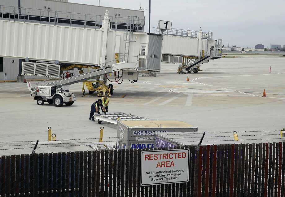 Workers move equipment near Hawaiian Airlines gates at the San Jose airport, where a boy hopped a fence Sunday. Photo: Eric Risberg, Associated Press