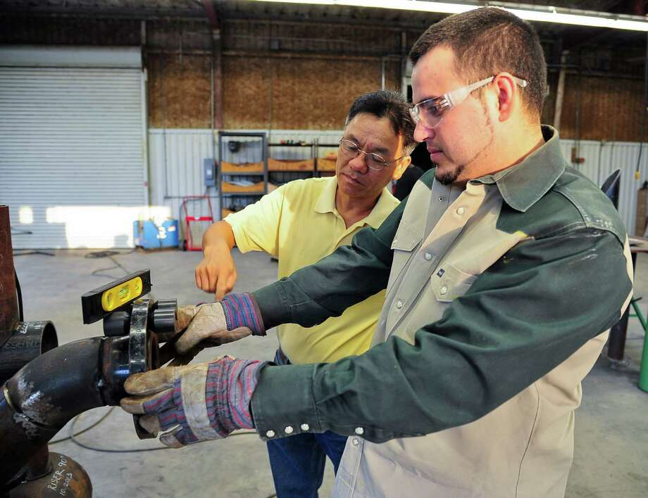 San Jacinto College pipefitting fabricator student Christian Cardenas-Gonzalez works on a class project under the supervision of pipefitting instructor Jay Nguong Nguyen (left).