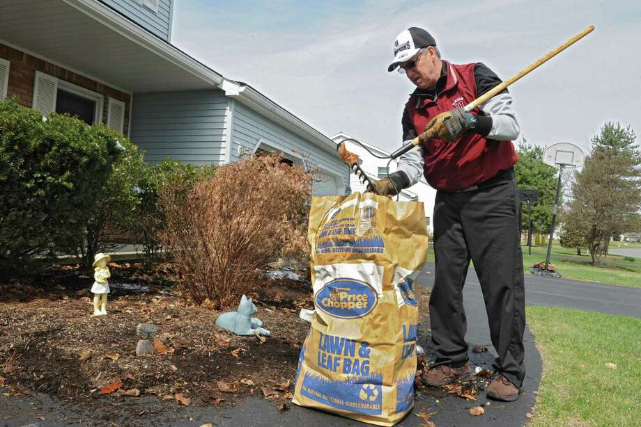 Mark Mindel rakes around his bushes as he works on his list of chores on Thursday, April 17, 2014 in Malta, N.Y. (Lori Van Buren / Times Union) Photo: Lori Van Buren / 00026530A