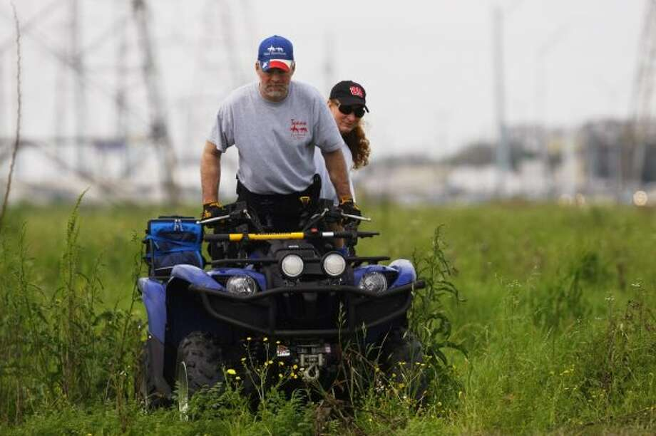 Volunteers with Texas Equusearch use ATVs to search along the Westpark Toll Rd. at Fondren for Kathy Lawson-Arrendondo, 37, who has been missing since Feb. 11.   (Johnny Hanson / Houston Chronicle)