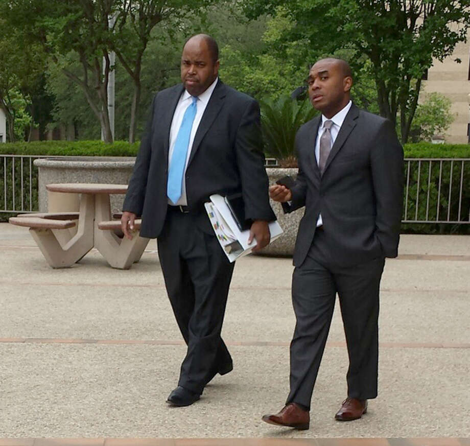 Leonard Roundtree III, right, leaves San Antonio's federal court with his lawyer, Curtis Lilly. Roundtree is on trial on charges that he agreed to help deliver a payment to a hitman his uncle, Alvin Roundtree, allegedly hired to kill his estranged common-law wife. Last June, Alvin Roundtree shot the woman seven times at Joint Base San Antonio -- Fort Sam Houston, but she survived. Photo: Guillermo Contreras, San Antonio Express-News / San Antonio Express-News