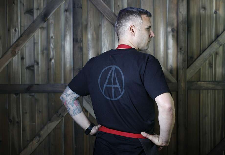 Dirty Habit chef David Bazirgan models the chef's outfit - a black T-shirt with red accents. Photo: Leah Millis, San Francisco Chronicle
