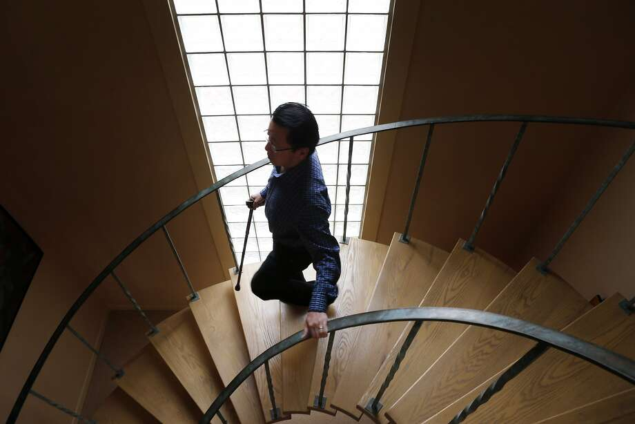 Ben Fong-Torres, who had hip replacement surgery in February, walks downstairs in his San Francisco home. Photo: Carlos Avila Gonzalez, The Chronicle