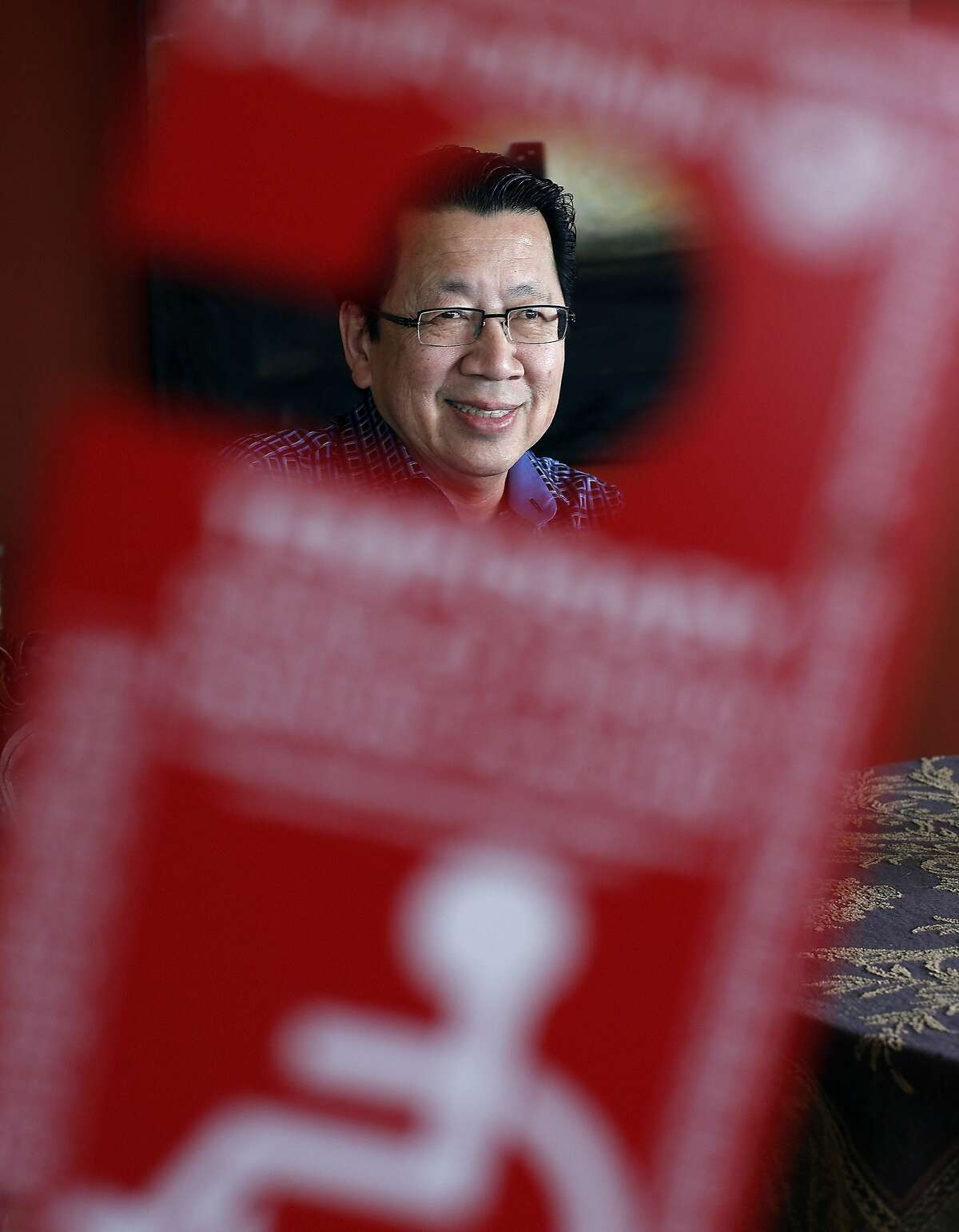 Journalist and author Ben Fong-Torres is seen through his temporary disabled parking placard in his San Francisco, Calif., home on Monday, April 21, 2014. Fong-Torres, who has recently recovered from hip replacement surgery, has largely returned to a normal walking routine, shedding his walker and for the most part his cane, which he says he really only uses for a sense of security.