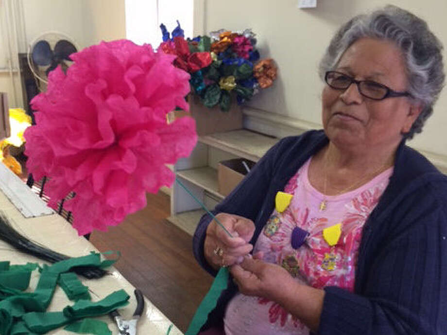 Beatrice Diaz's pink, handmade flower is a blur as she spins green wrapping on a wire stem. Diaz is one of the women who make blooms for the Battle of Flowers parade. Photo: Vincent T. Davis / Southside Reporter