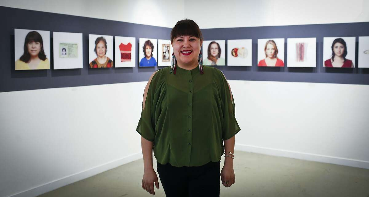 Executive Director Ani Rivera stands in front of works by Alejandra Regalado inside the gallery on 24th Street.