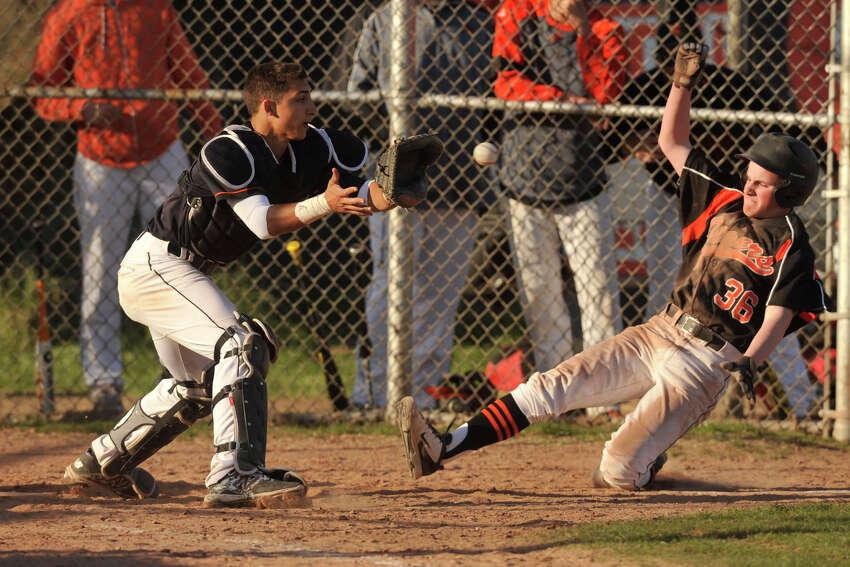 Ridgefield's Zachary Fogg beats the throw home to Stamford catcher Tyler Serrichio during their baseball game at Stamford High School in Stamford, Conn., on Monday, April 21, 2014. Ridgefield won, 7-4.