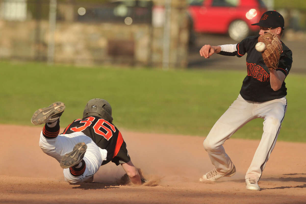 Ridgefield's Zachary Fogg slides safely into second beating the tag from Stamford second baseman Jay Devito during their baseball game at Stamford High School in Stamford, Conn., on Monday, April 21, 2014. Ridgefield won, 7-4.