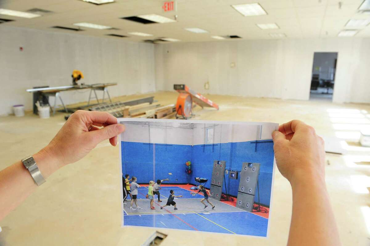 Owner, Sheri Townsend holds a photograph of what the gross motor room will look like when completed at the Bizzy Beez Activity Center on Monday, April 21, 2014, in Colonie, N.Y. The gross motor room will allow children to work on eye, hand and motor coordination. The building when finished will be the new location of the Spotted Zebra Learning Center and the Bizzy Beez Activity Center. (Paul Buckowski / Times Union)