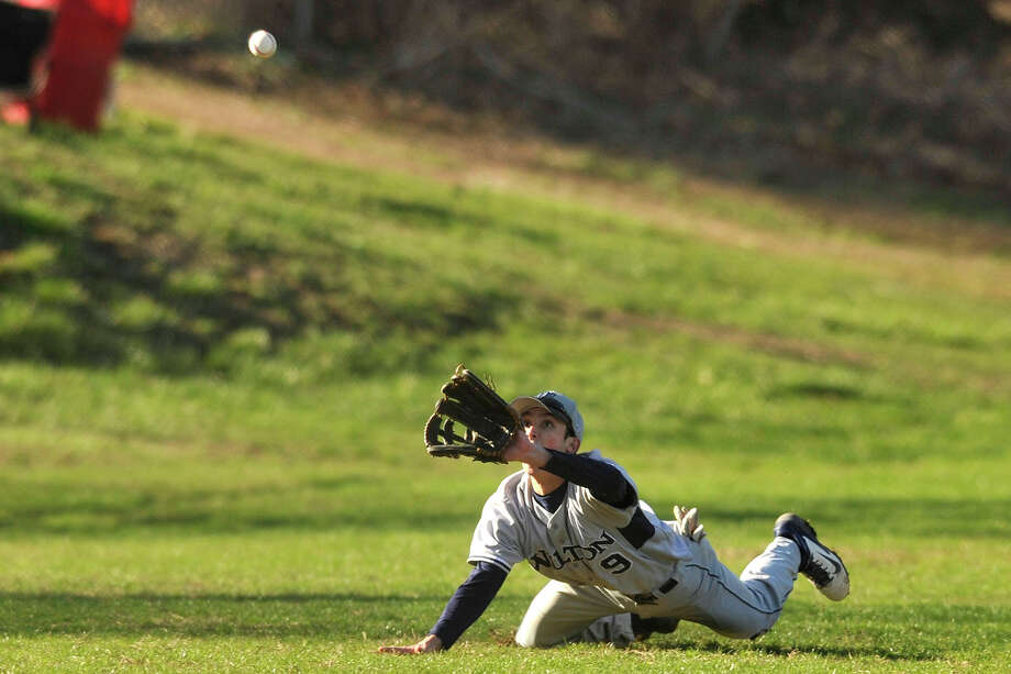 Wilton left fielder James Meany attempts to make a diving catch during the Warriors' baseball game against Westhill at Westhill High School in Stamford, Conn., on Wednesday, April 16, 2014. Westhill won, 9-0. Photo: Jason Rearick / Stamford Advocate