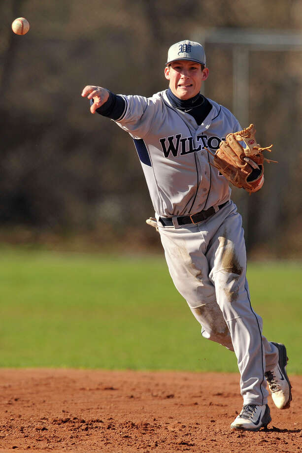 Wilton shortstop Brett Phillips fires the ball to first during the Warrriors' baseball game against Westhill at Westhill High School in Stamford, Conn., on Wednesday, April 16, 2014. Westhill won, 9-0. Photo: Jason Rearick / Stamford Advocate